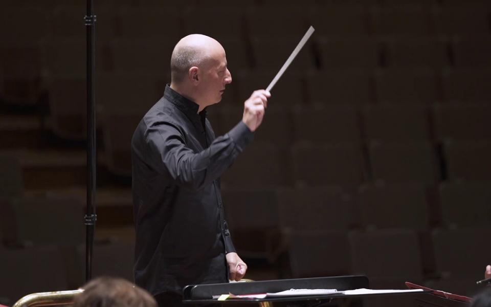 Paavo Järvi conducting on stage, holding up his baton