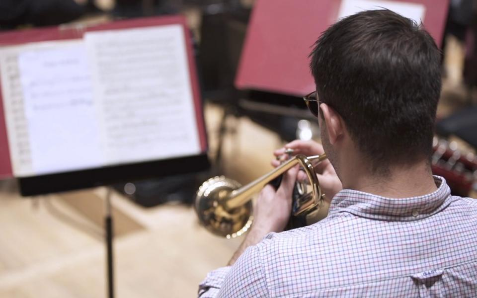 Philharmonia trumpet player rehearsing on stage