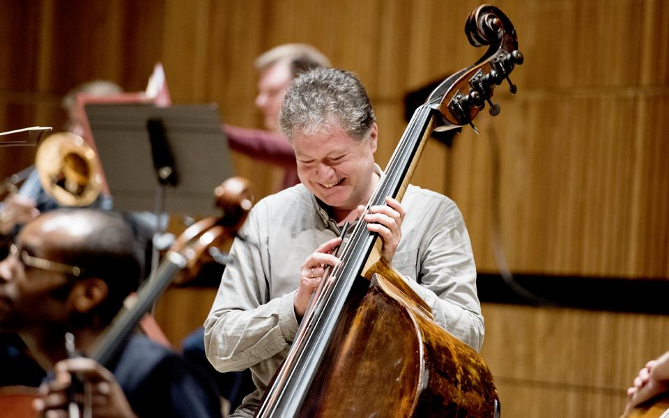 Christian Geldsetzer smiling, holding a double bass, waering casual clothing
