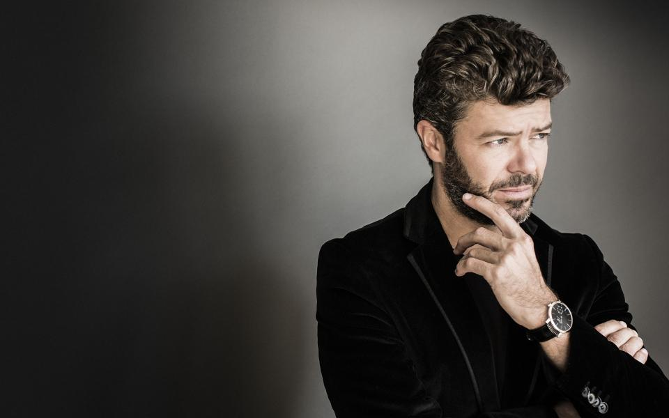 Conductor Pablo Heras-Casado wearing a black velvet blazer, holding his hand to his face, looking off camera