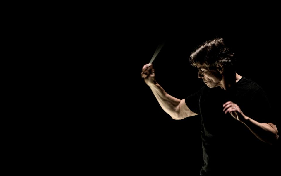 Conductor Esa-Pekka Salonen againt an all-black background, conducting