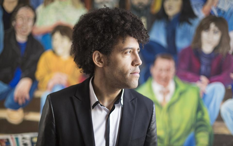 Conductor Rafael Payare wearing a black blazer over a white shirt, looking off camera, against a mural featuring people seating on stalls