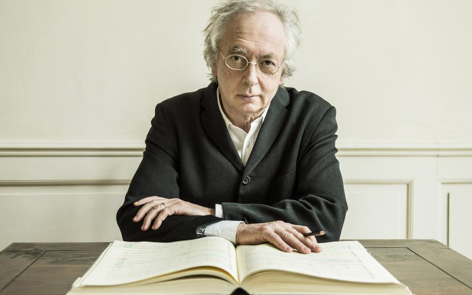 Conductor Philippe Herreweghe, sitting at a table with a pencil in his hand, going over a score