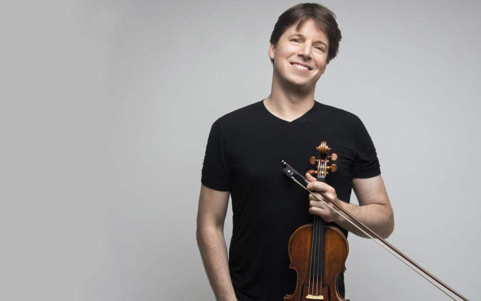 Violinist Joshua Bell, wearing a black t-shirt, holding his violin and smiling at camera
