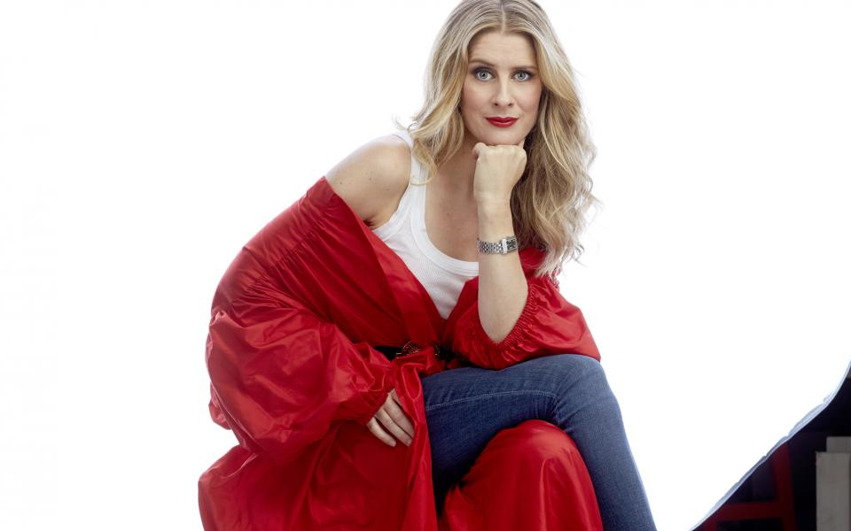 Soprano Malin Byström sitting down, wearing a red cape over jeans and a white t-shirt, looking at the camera with her chin on her hand