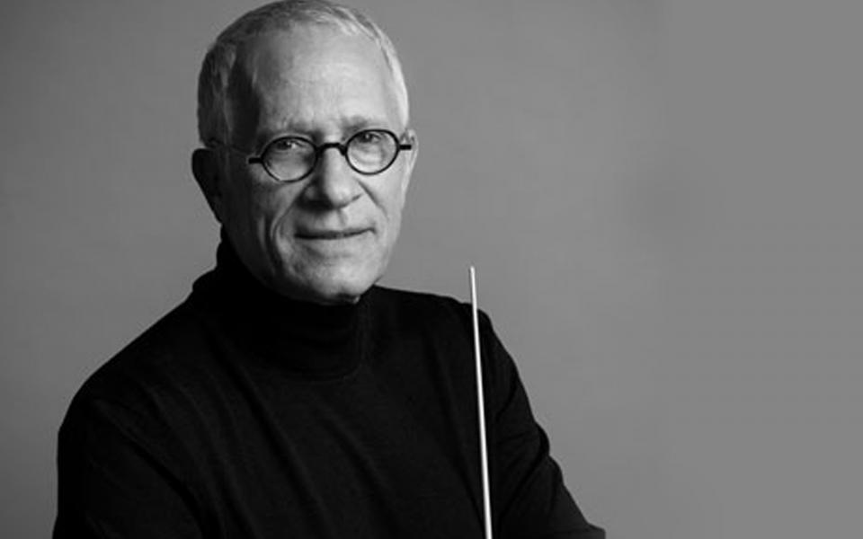 Conductor James Newton Howard holding a baton, wearing glasses and a black turtleneck