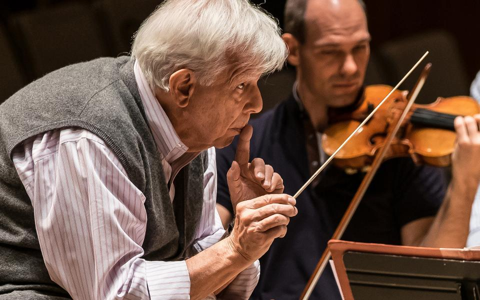 Christoph von Dohnanyi on stage, holding a finger to his lips and a baton in the other hand, at rehearsal, on stage