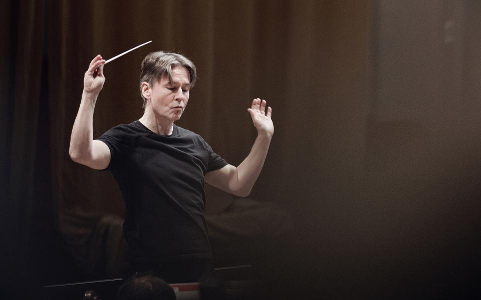Esa-Pekka Salonen on stage, holding a baton, wearing a black t-shirt