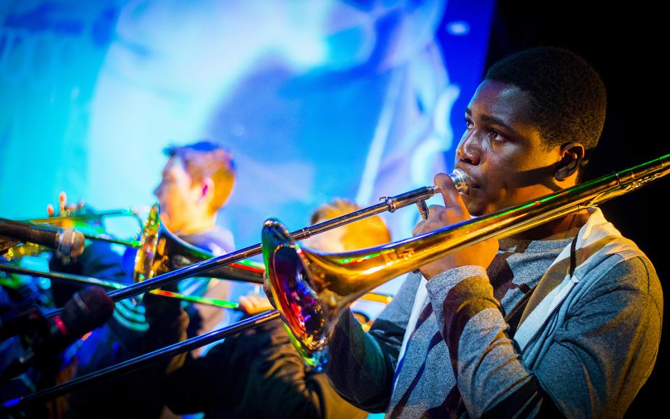 A young man plays trombone at Symphonize culmination event, Leicester, 2018