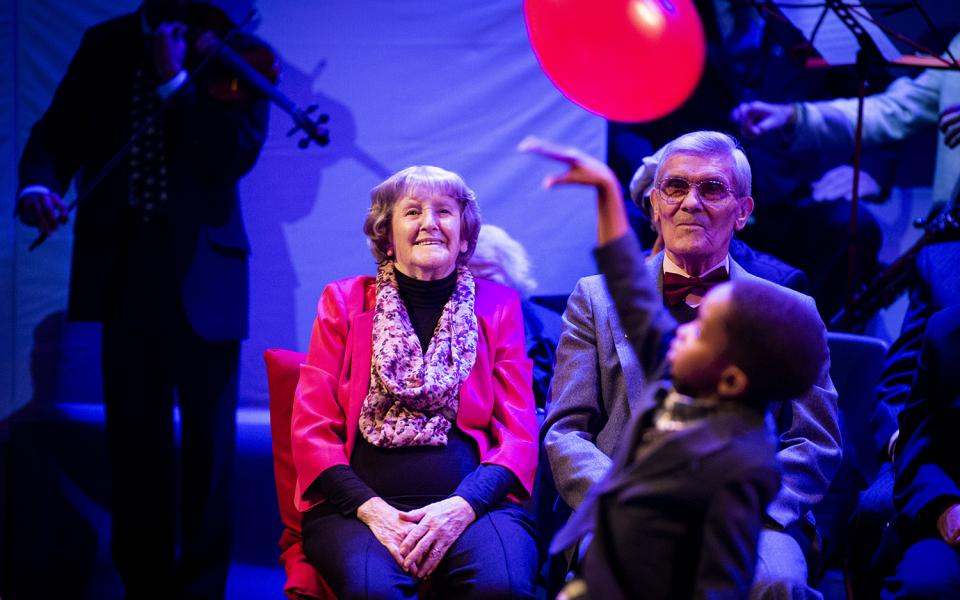 A couple watch a small boy play with a red ballon at the Hear and Now culmination performance, 2019
