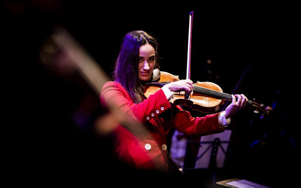 Violinist wearing a red suit at Hear and Now culmination performance, 2019
