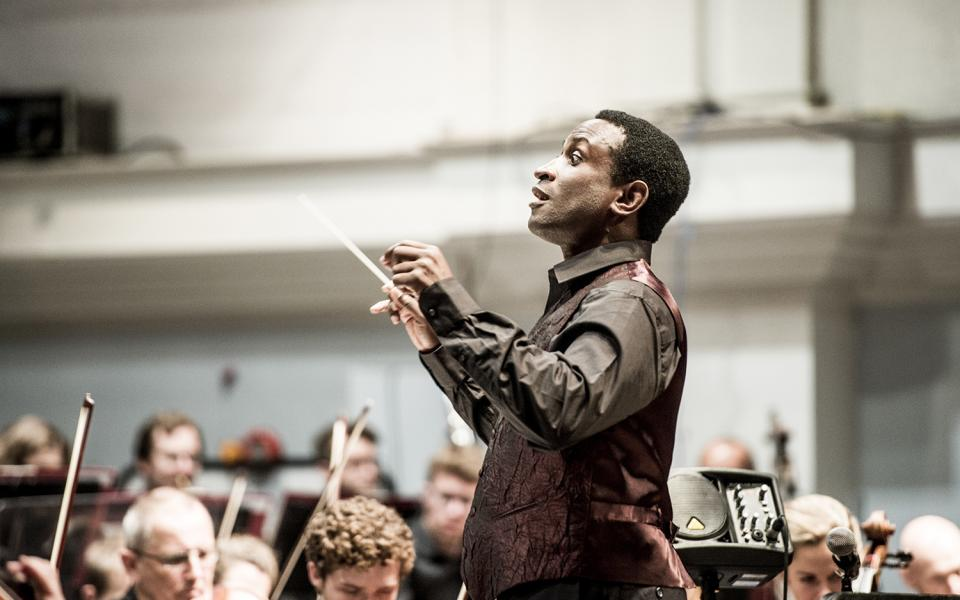 Kwamé Ryan conducting the Philharmonia, wearing a vest