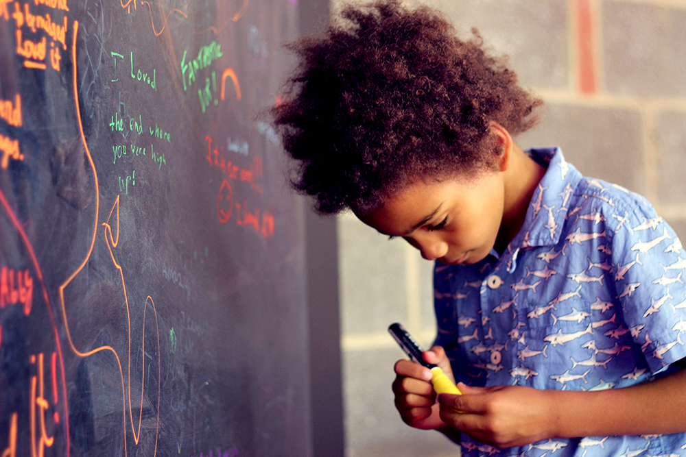 Boy at The Virtual Orchestra, holding a marker in front of a wall that has inscriptions of different colours