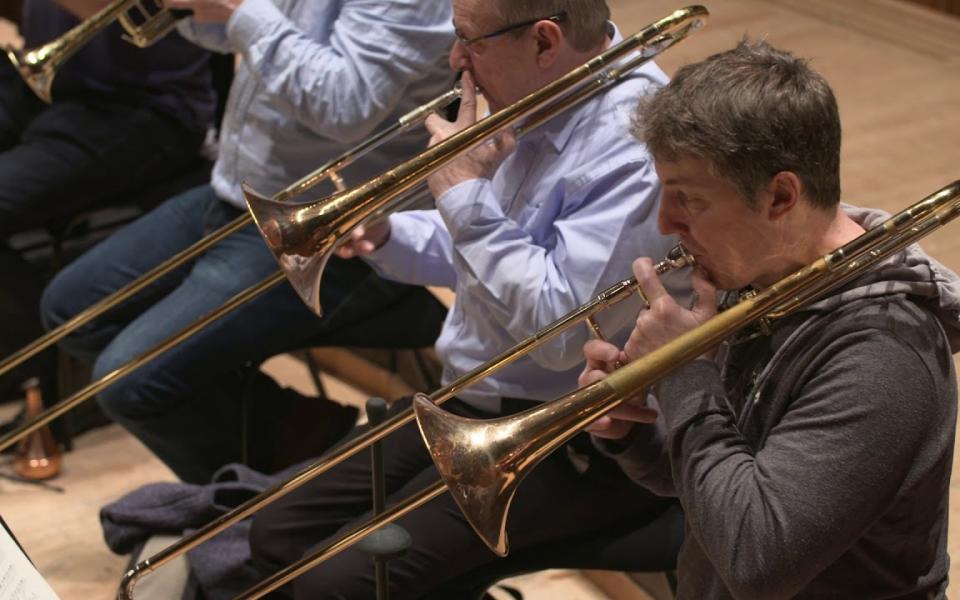 Philharmonia trombones rehearsing on stage