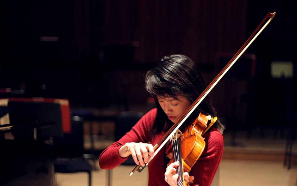 Julia Liang, from the Philharmonia MMSF Instrumental Fellowship Programme plays the violin on stage in rehearsal