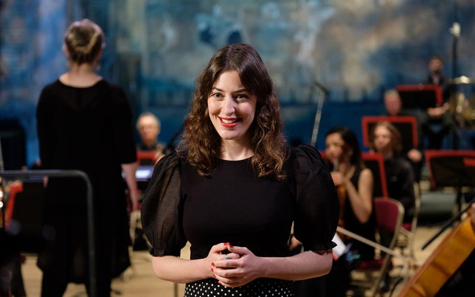 Photo of presenter Lucy Drever at the Philharmonia Sessions, smiling, Philharmonia Orchestra in the background